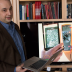 Professor Vladimir Bulović discusses research that led to transparent solar cells, which can power an electronic book reader, as shown in video on television screen behind him. An MIT spinoff, Ubiquitous Energy, based in Redwood City, California, is commercializing the technology. Photo: Denis Paiste/Materials Processing Center