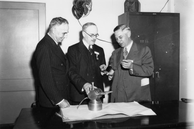 Henry Thomas Tizard (center), British physicist and head of the Tizard Mission, visits with MIT researchers. The 1940 Tizard Mission introduced to the U.S. the newly invented resonant-cavity magnetron and other British radar developments, and helped establish MIT as a major federally funded research university.  Photo courtesy of the MIT Museum.
